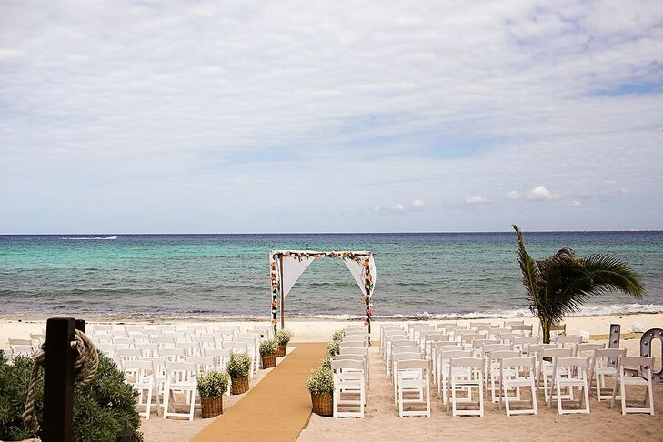 Marta and Jose Luis exchanged their vows on the beach under this linen-draped wedding arch. Potted greenery lined the aisle.