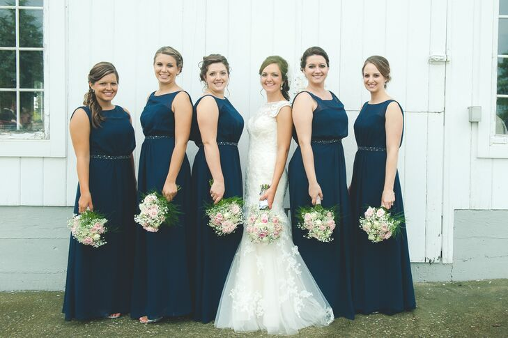 Stephanie stood in the middle of her bridesmaids, who wore long navy dresses while holding their bouquets.