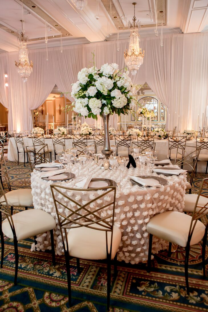 Centerpieces included dome shaped arrangements of white hydrangeas, white roses and greens in tall mercury vases. The ballroom in which the reception was held featured antique crystal chandeliers.