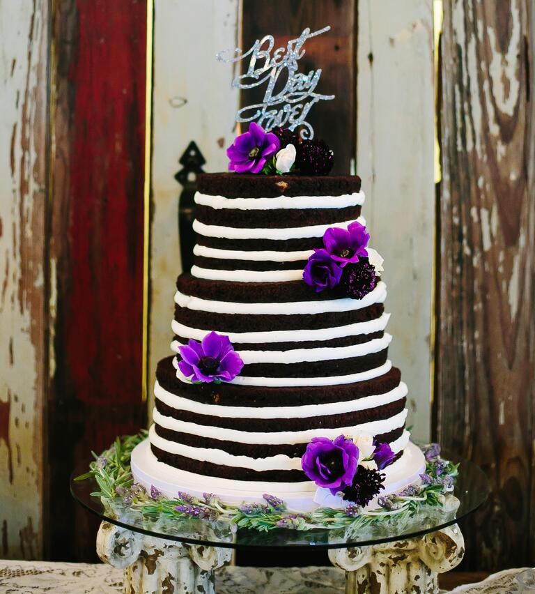 Chocolate and vanilla naked cake with bright purple flowers