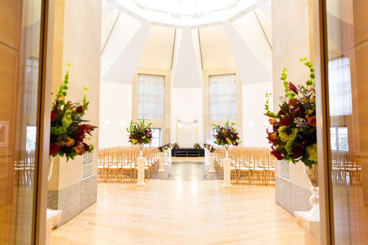 The ceremony was held in the Ronald Reagan Building's pavilion, a round room with high ceilings, and beautiful bright skylights. The aisle was simply lined with white columns topped with autumnal floral arrangements.
