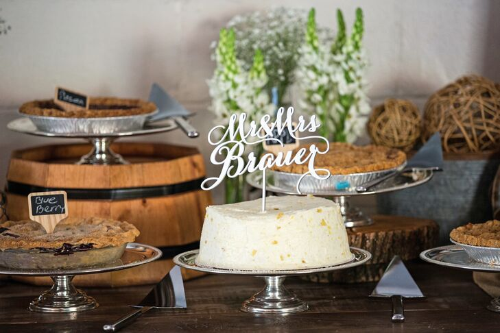 "Elena and Greg served a variety of pies—including a white creamy masterpiece displayed on top of a silver stand—instead a wedding cake. The dessert had a white ""Mr. & Mrs. Brauer"" topper that added a personal touch to the pie."