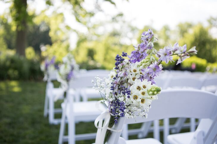 Bunches of purple and white blooms (including lavender, of course) had a white piece of ribbon tying the arrangement together, which accented the ends of folding chairs lining the aisle at the ceremony.