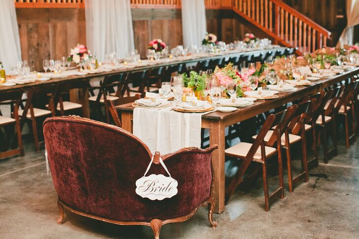 "Lydia and Brandon took their seats at the head of one of the long family-style dining tables at Olympia's Valley Estate in Petaluma, California. The newlyweds sat on the burgundy velvet love seat with ""bride"" and ""groom"" signs marking their territory."