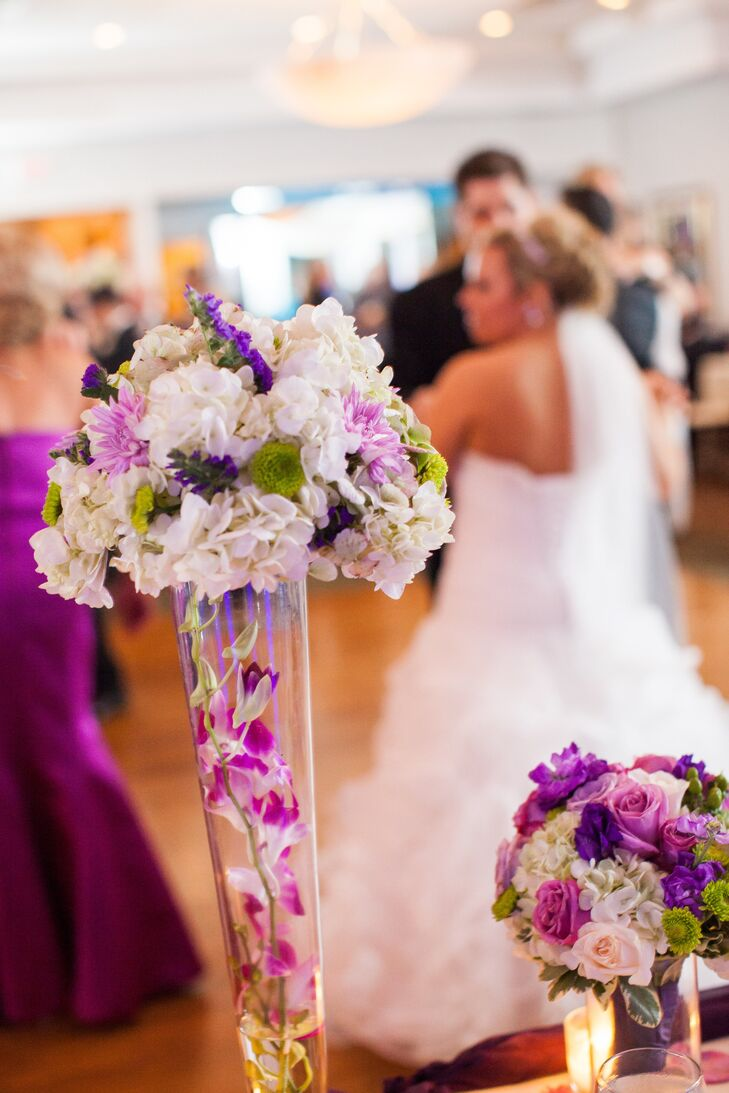 On the main table, tall white and purple flower arrangements sat in glass vases filled with purple orchids. Smaller arrangements were also used for contrast.