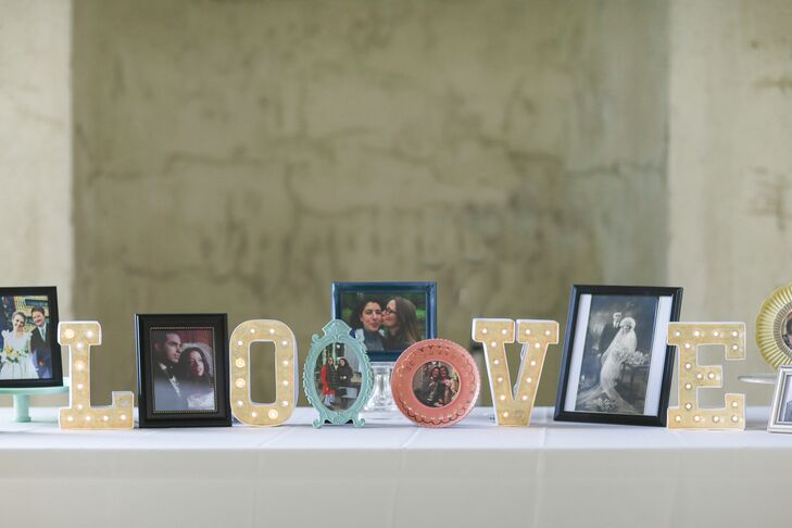 "Their day was based on tradition, friends and family. So when guests walked into the reception, it was no surprise that Elana and Jamie literally celebrated their guests with this heartfelt photo display. Pictures of themselves and loved ones filled the table among colorful marquee letters that spelled ""love."""