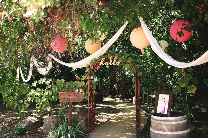 "Guests entered the outdoor ceremony space through a wooden wedding arch with a sign above that read ""Hello"" in gold letters. A sign pointed through the wedding arch, letting friends and family know where the ceremony was located. White linens and colorful paper lanterns hung from tree branches."