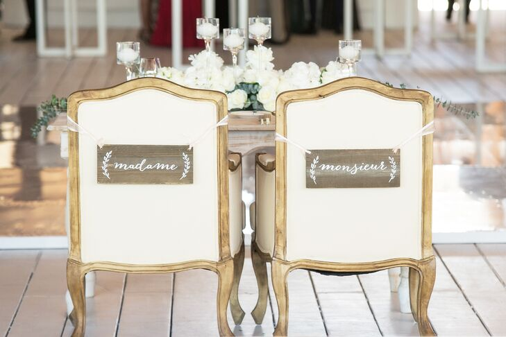 "In a nod to their family's French heritage, Michelle and Vincent had wooden ""Madame"" and ""Monsieur"" signs tied to their sweetheart table seats with crisp white tulle."