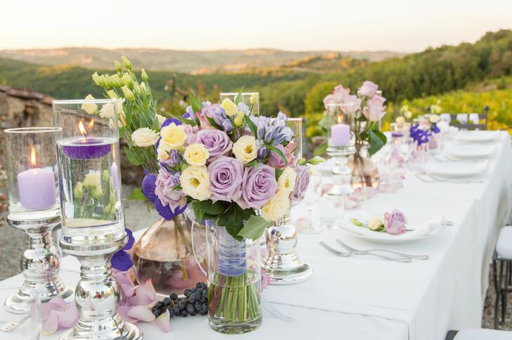 Centerpieces of yellow, ivory and purple roses in glass vases decorated the long white dining table at the reception.