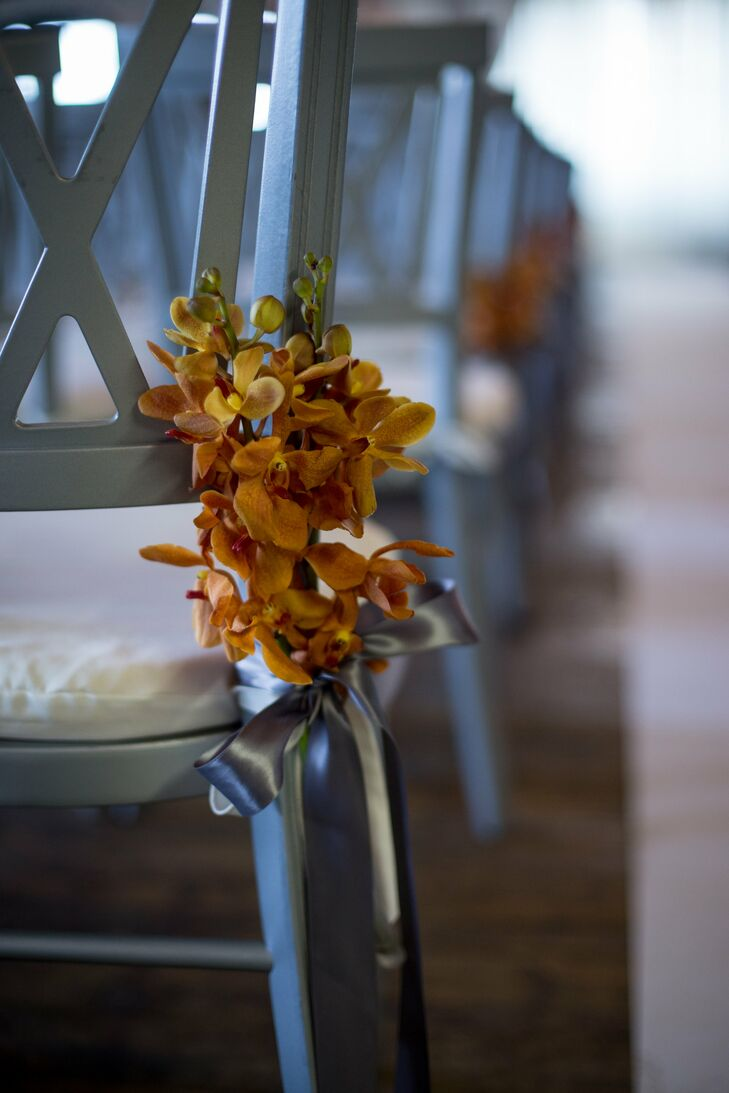 Simple orange blooms adorned the side of each silver chair during the couple's indoor wedding ceremony.