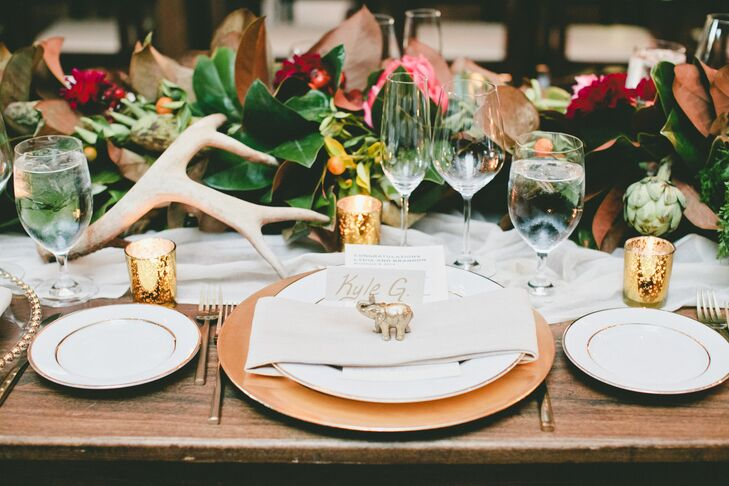 A gold elephant decorated each setting on the wooden dining tables, positioned near the white and gold escort card. White and gold plates contributed to the overall color scheme of the elegant dining display.