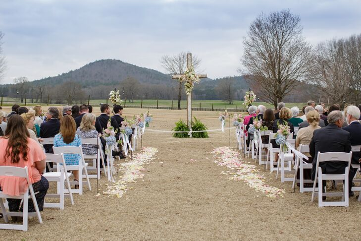 """Our florist, King's Garden [Susan Huff and Beth Jordan], knew the look we wanted and they just ran with it,"" Mary Caroline says. On Mary Caroline and Forrest's wedding day, white and pink flower petals lined the aisle as arrangements of hydrangeas and delphiniums were hung alongside the first few rows of white folding chairs. Lush white and pink blooms also accented their wooden cross."