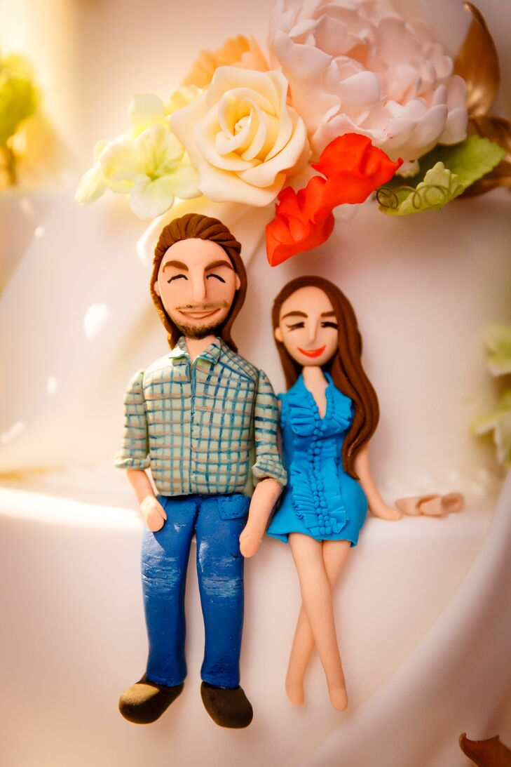 "Instead of a traditional cake topper, Lauren Bohl White of A White Cake created fondant figurines in the likeness of Allison and Jason. The figurines were displayed on the side of the cake, amongst elegant folds of fondant and elaborate sugar flowers. ""Our cake was layered coconut cake with vanilla cream and lemon cake with lime curd,"" says Allison. ""It was amazing!"""