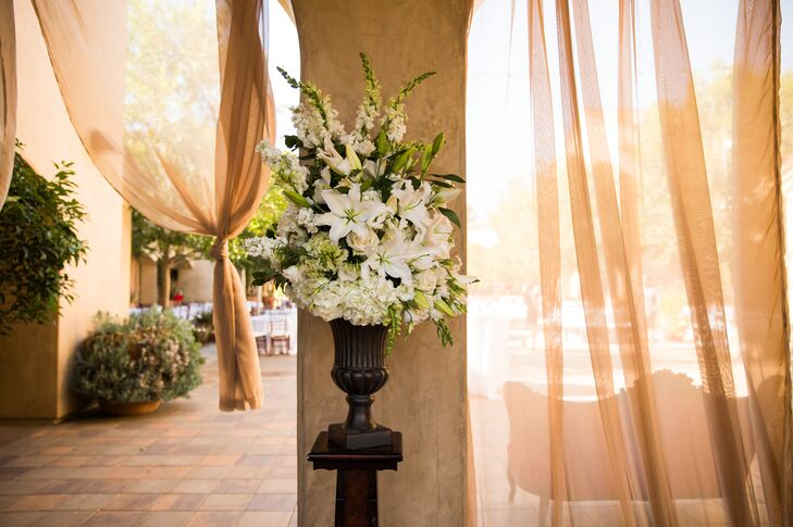 Ivory lilies, hydrangeas, roses and stock were mixed with greenery to create an elegant flower arrangement, placed inside a dark wooden vase that was propped up on a pedestal.
