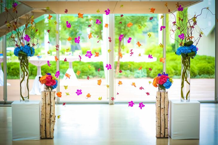 """My favorite element was our flower curtain,"" Maria says. The breathtaking ceremony backdrop included blue hydrangeas and hot pink, orange, red and green orchid blossoms to brighten the monochromatic modern space."