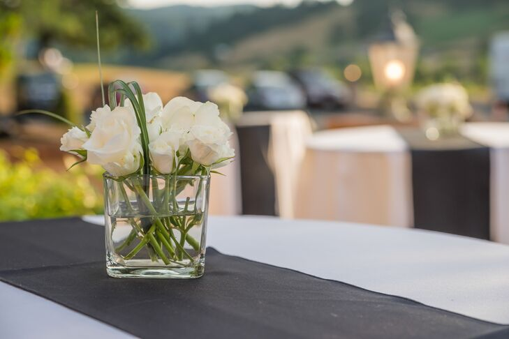 Outside at the vineyard, cocktail tables draped with white linens and black runners filled the space. Low white rose arrangements filled glass vases, which decorated the middle of tables.
