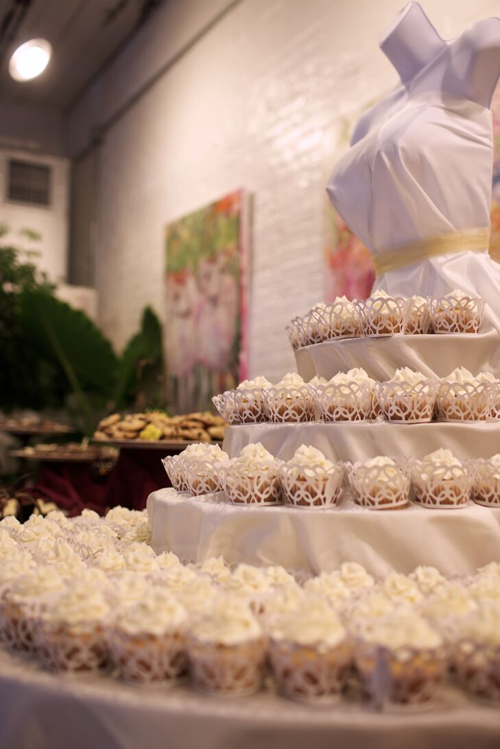 White cupcakes, provided by Elizabests, were arranged on a tiered stand surrounding an artsy bust.