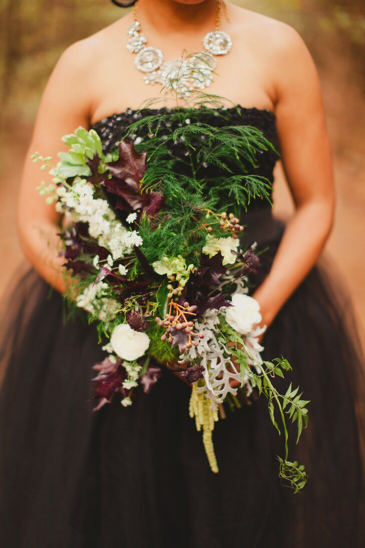 A winter forest bouquet was created out of lush, sculptural greenery, blackberries and black and white blooms.