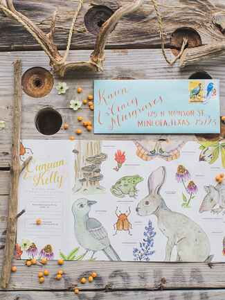 Whimsical wildlife illustrations on a rustic wedding invitation suite