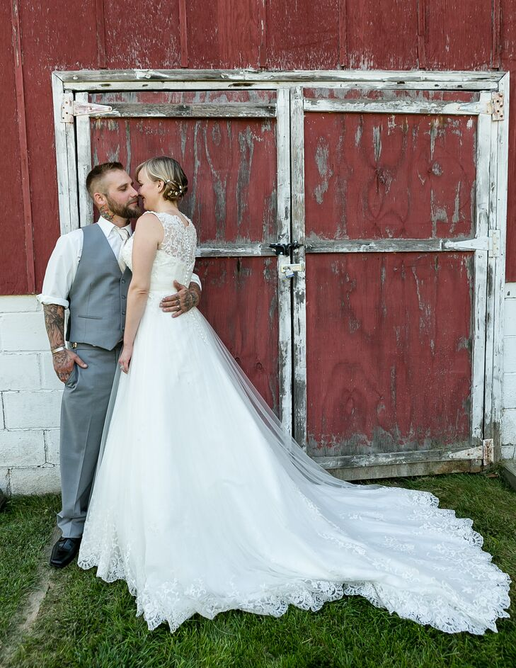 Megan and Clint embrace each other in front of a red rustic barn.