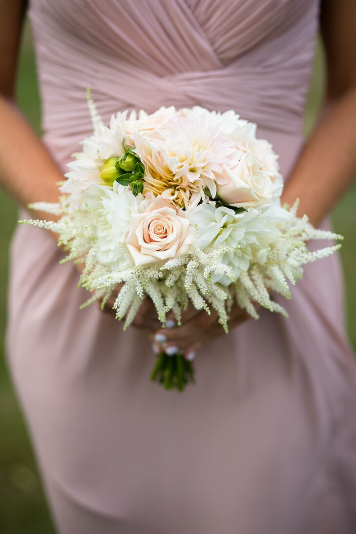 The couple's florist from Beautiful Days created whimsical bouquets to complement each bridesmaid's different-style rose dress. The arrangements added a cohesive element to their looks with white astilbes, white roses, white hydrangeas, blush dahlias and greenery. The bouquets also complemented Caitlin and Mike's natural farm venue.