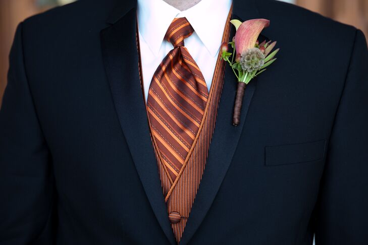 The groomsmen wore black tuxedos with striped burnt orange vests and ties.