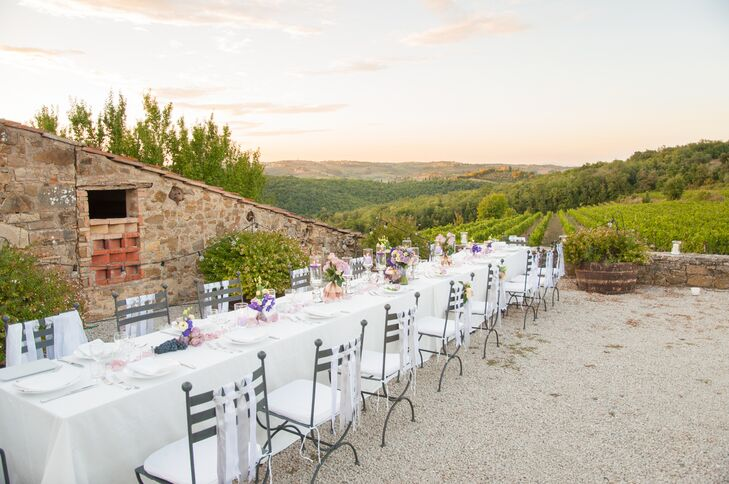 The couple had their reception at Quercia al Poggio located in Florence, Italy. The long reception dining table with white linens and accents overlooked the green vineyards and Tuscan hills.