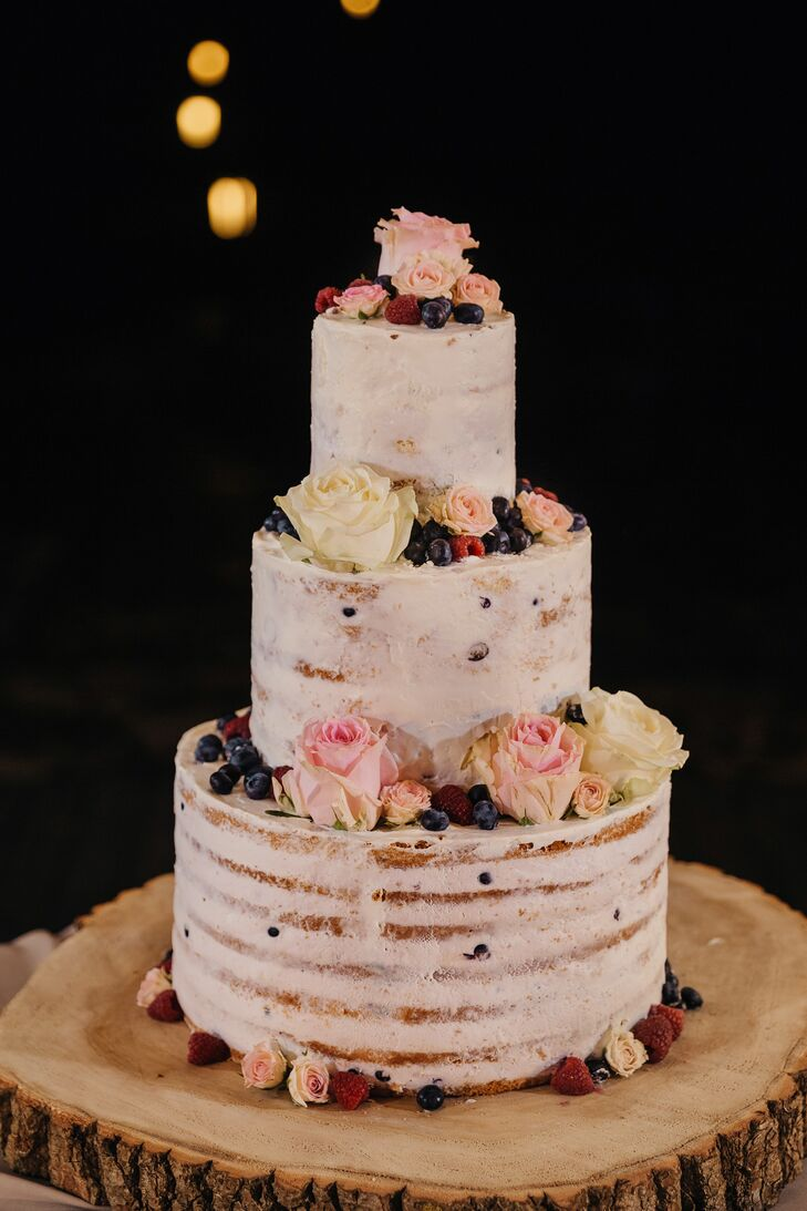 "Katya and Nikita's three-tier naked cake was embellished with berries and blooms. ""It was as delicious as it looked,"" the bride says."