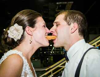 Bride and groom share a donut