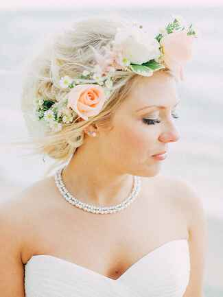 Messy wedding updo with a flower crown made with roses and daises