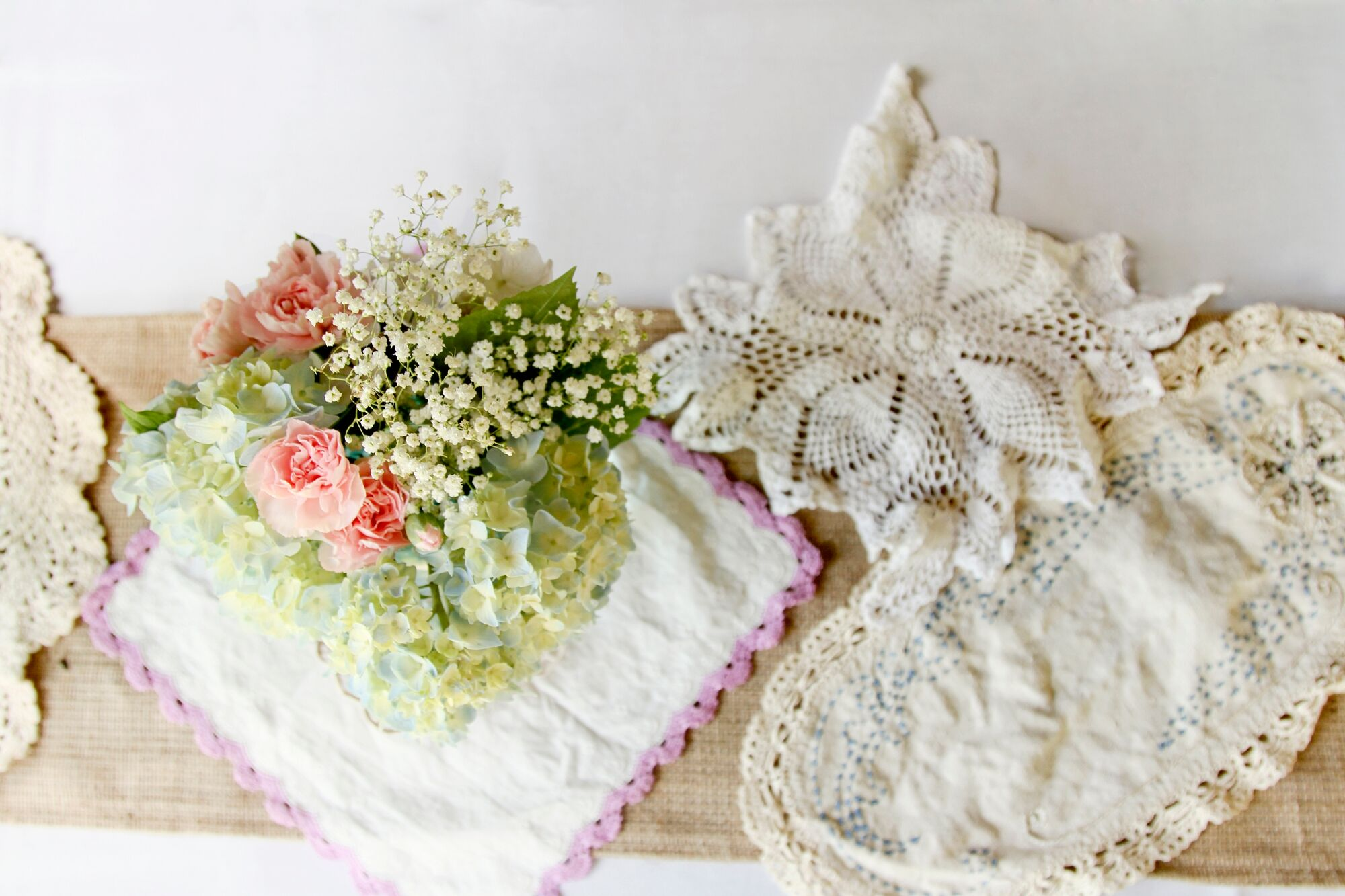 Centerpieces On Burlap Table Runner And Lace Doilies