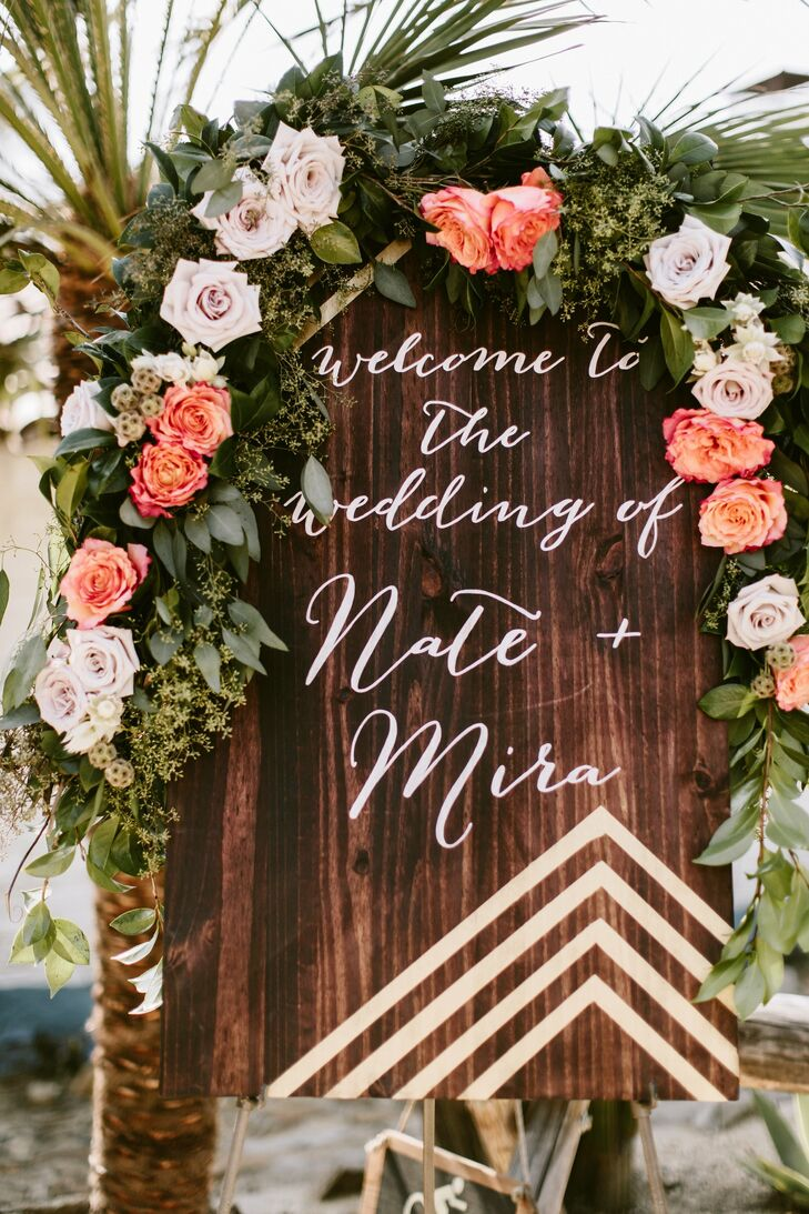 Sunset-hued floral garlands were used throughout the event. Here, one is draped over a wooden welcome sign.