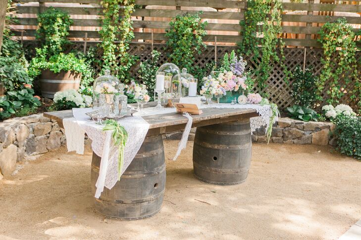 The guest book table was one of the aesthetic highlights of the evening. The rustic display featured a wine barrel table dressed to the nines with delicate lace linens, silver trays and candlesticks, romantic garden roses and bell jars filled with mini topiaries.