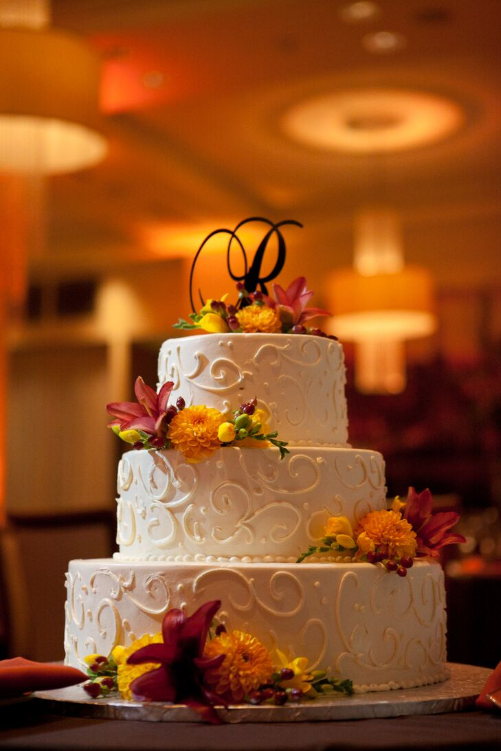 "Sara and Rob's three tier wedding cake was finished with ivory frosting and elegant swirl detail and a cascade of fresh blooms in the day's color palette. A monogram letter ""R"" finished the confection."