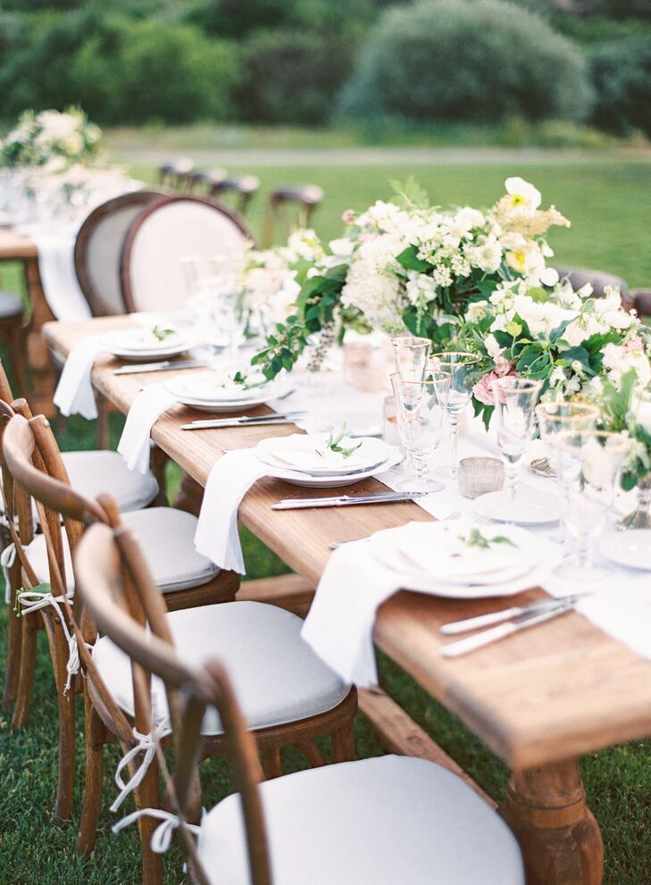 Overflowing bowls of peonies, garden roses, sweet peas, phlox and ranunculus covered the long wood tables. Vineyard-style chair flanked the feasting tables for the alfresco reception dinner.