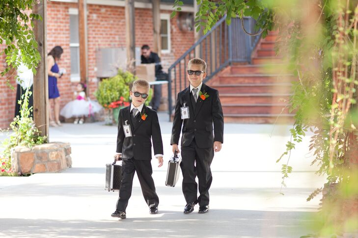 "The ring bearers, lovingly dubbed ring security, wore black tuxedos to match the groomsmen, silver ties, black sunglasses and carried gun cases for the rings. They walked down the aisle to ""Men in Black"" by Will Smith."