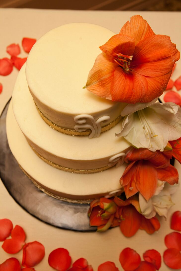 "The three-tiered ivory wedding cake was decorated in coral and ivory lilies. ""The first layer was chocolate with raspberry filling, the middle was an Oreo cake and the top layer was red velvet,"" says Shantelle. ""It had butter cream frosting along with lilies and gold ribbon at the base."""