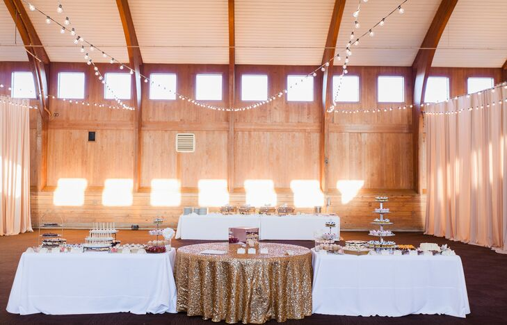 Tables covered in white and gold shimmery linens displayed a wide range of desserts made by friends and family at the reception, with strings of lightbulbs dangling above.