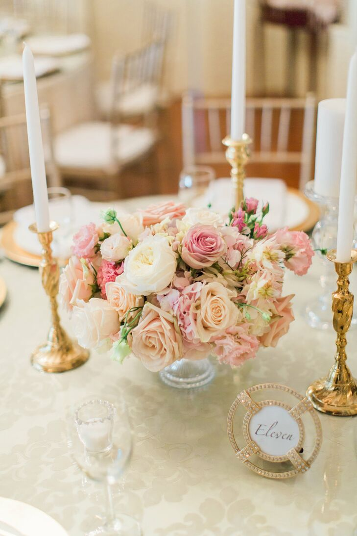 Gold candlesticks and embellished frames topped round reception tables, along with low-lying centerpieces made of white ranunculus and pink roses.