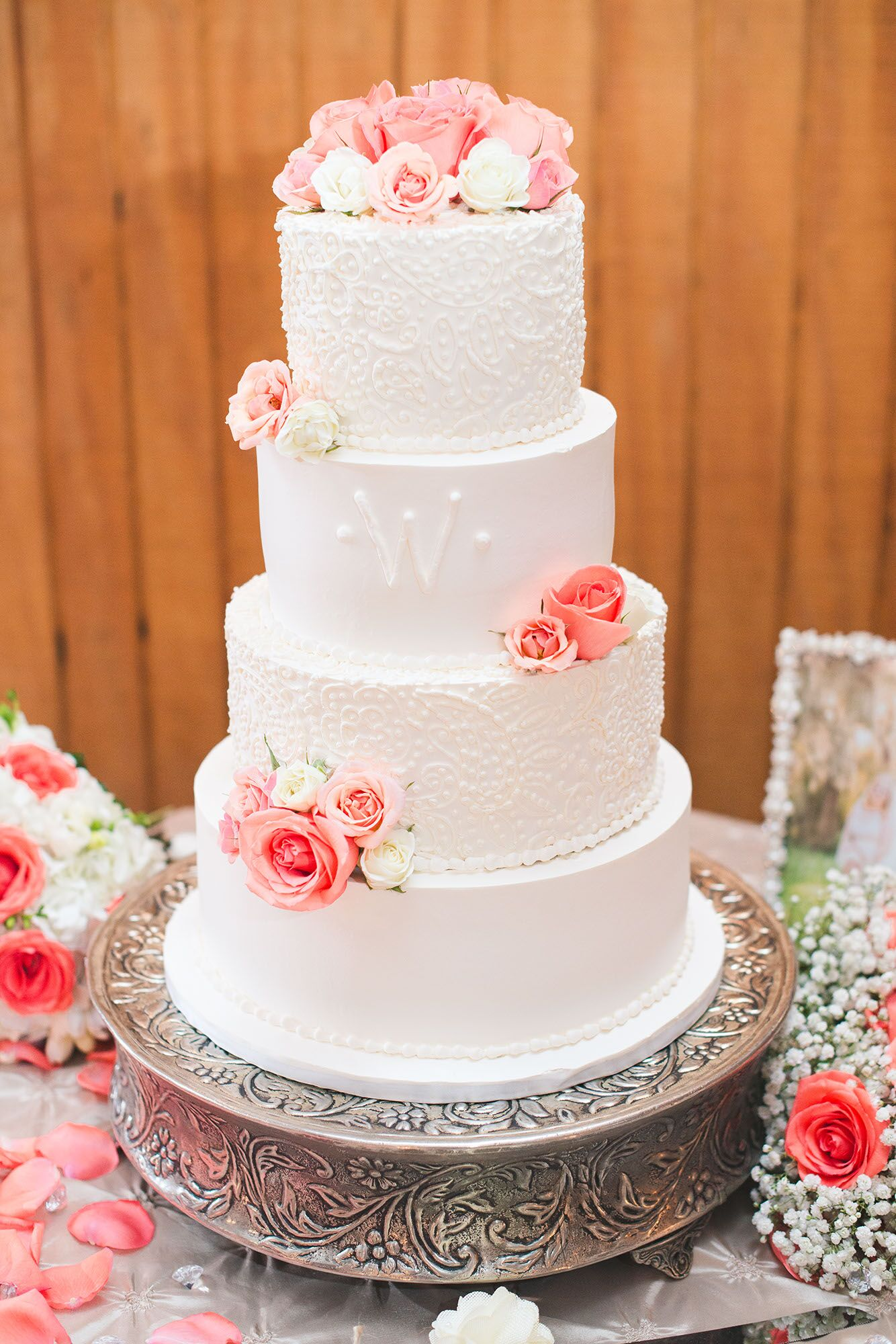 detailed white wedding cake with coral roses