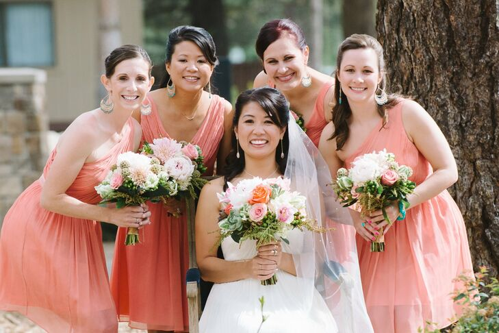 The bridesmaid wore short one-shoulder and v-neck dresses in a cheerful shade of coral pink.