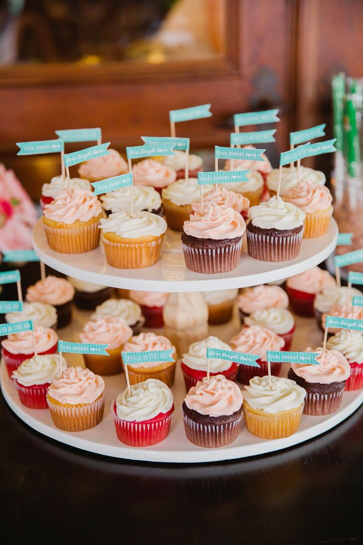 Sweet cupcakes frosted in ivory and blush were topped with blue flags at the dessert table.