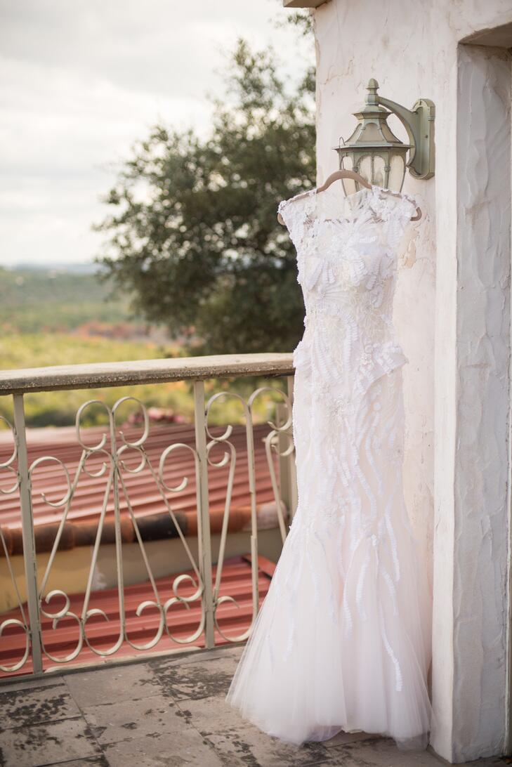 Monique Lhuillier wedding dress hangs on a hanger