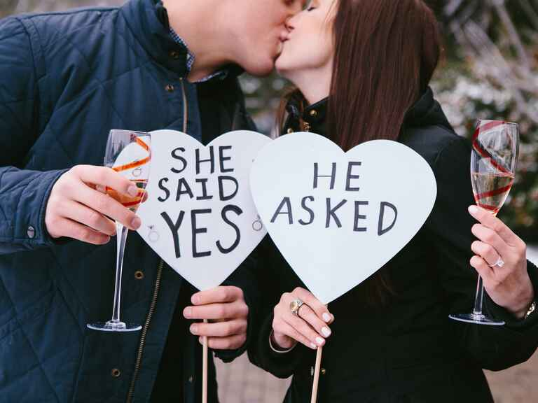 Heart-shaped photo props and champagne for an engagement announcement photo