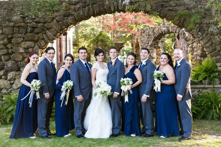 The bridesmaids wore floor-length navy gowns in a variety of styles, while the groomsmen sported classic gray suits and navy ties.