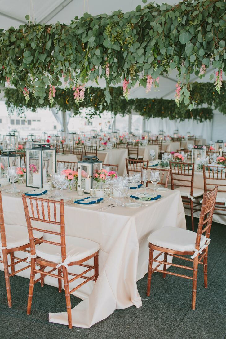 The white wedding tent was decorated with hanging eucalyptus. Reception tables had lantern and small votive centerpieces with coral-toned flowers and eucalyptus.
