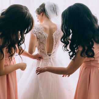 bridemaids helping the bride get into wedding dress