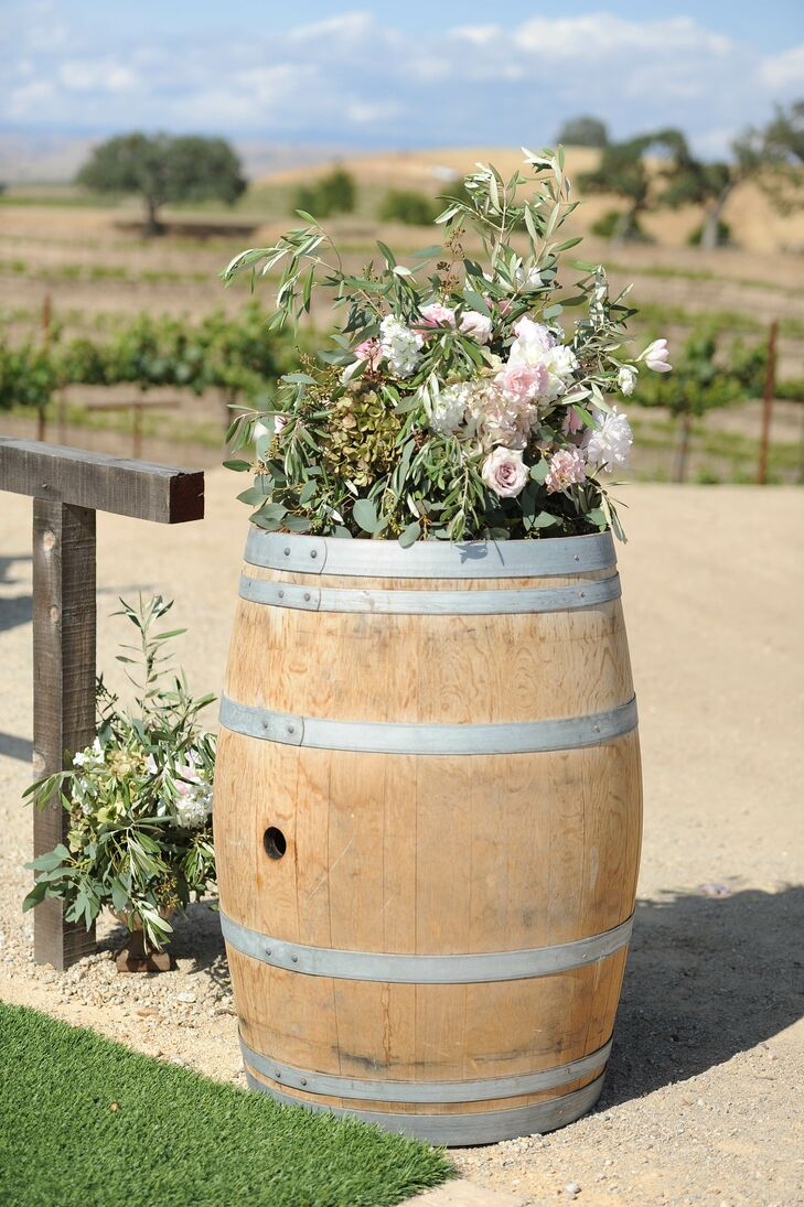 The couple kept the decor to a minimum but added a few details such as blush peonies and roses displayed atop wine barrels.
