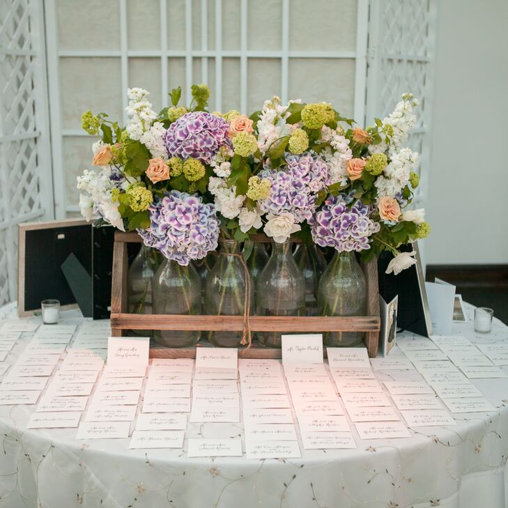 On the place card table, Alexandra and Will's florist, Rebecca Shepherd Floral Designs, created a unique flower arrangement using glass vases of purple, coral and white roses, hydrangeas and stock and placing them in a wooden milk crate.