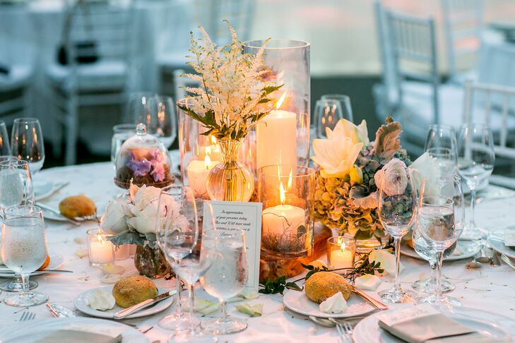 "Alexandra and Will's wedding florist, Rebecca Shepherd Floral designs, decorated the reception table centerpieces with various flowers, including roses, peonies and irises, and warm candlelight. ""She used bell jars and antique candlesticks to add to the centerpieces,"" Alexandra says."